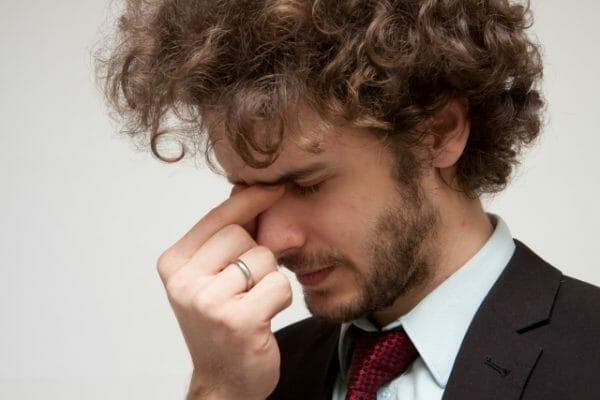 ストレスが原因で偏頭痛・慢性頭痛に悩む男性の画像