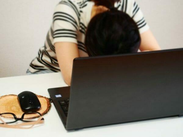 眠くて仕事や家事の能率が上がらないと悩んでいる女性のイメージ
