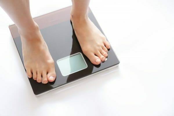 肩と首に肉がつく太り方で悩む人が体重を測っているイメージ