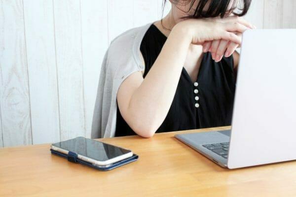 日中の眠気に耐えきれず仕事が進まず悩む女性のイメージ