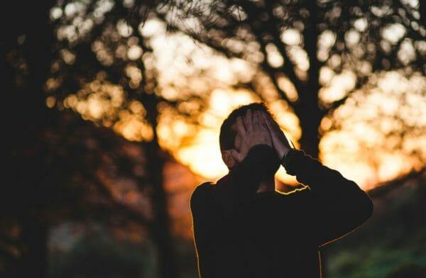 ストレスを抱えて頭を手で覆っている男性の写真
